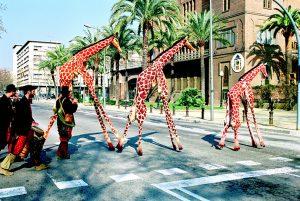 Două girafe și puiul lor se plimbă pe străzile orașului pe un fond sonor care recreează auditiv sunetele savanei